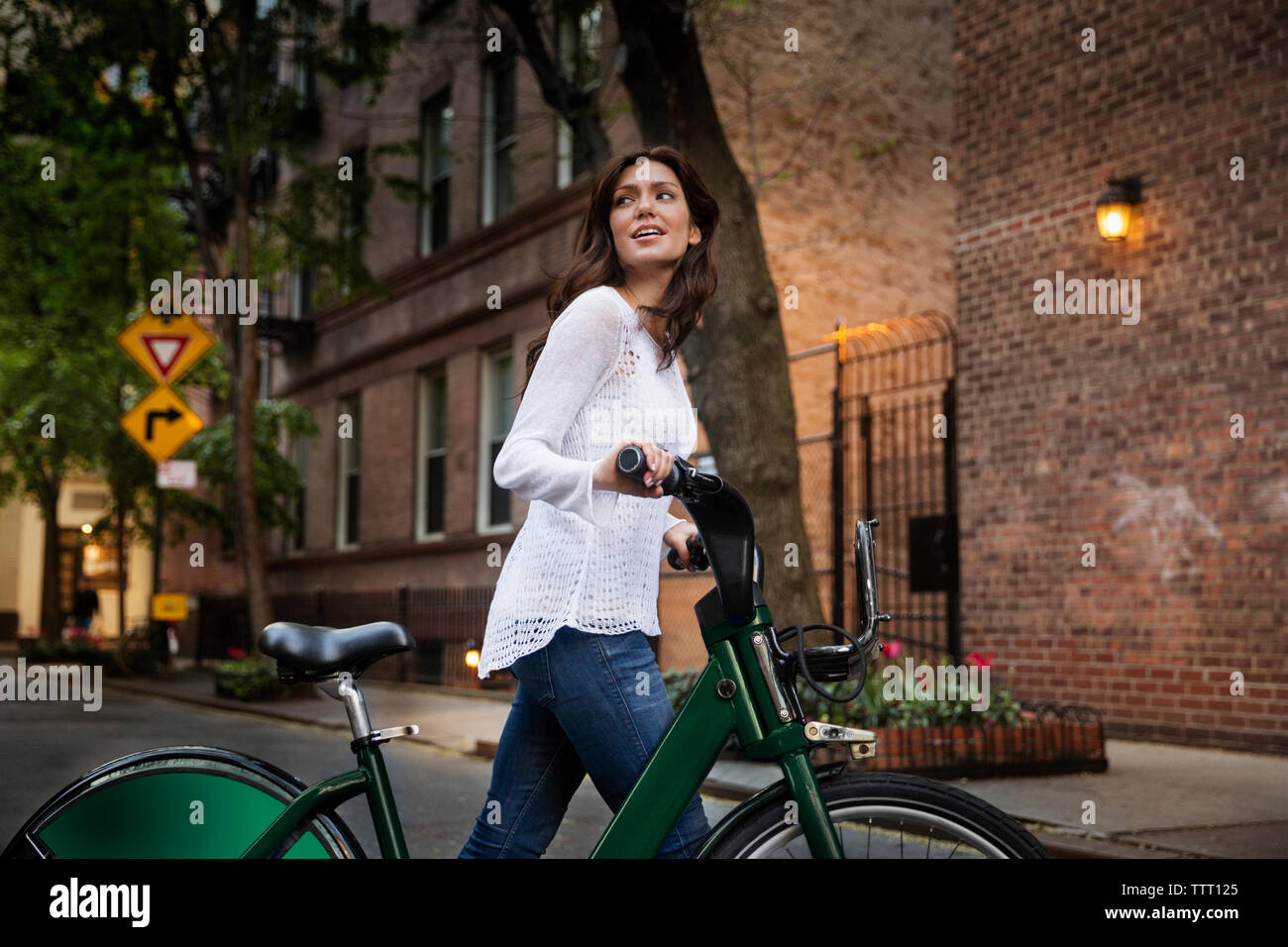 Young woman walking with bicycle on street Stock Photo