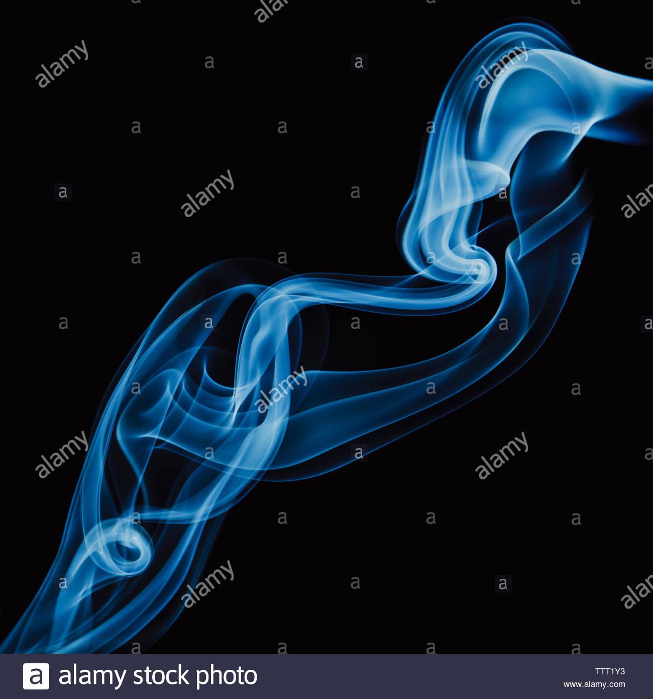 Close-up of smoke against black background - Stock Image