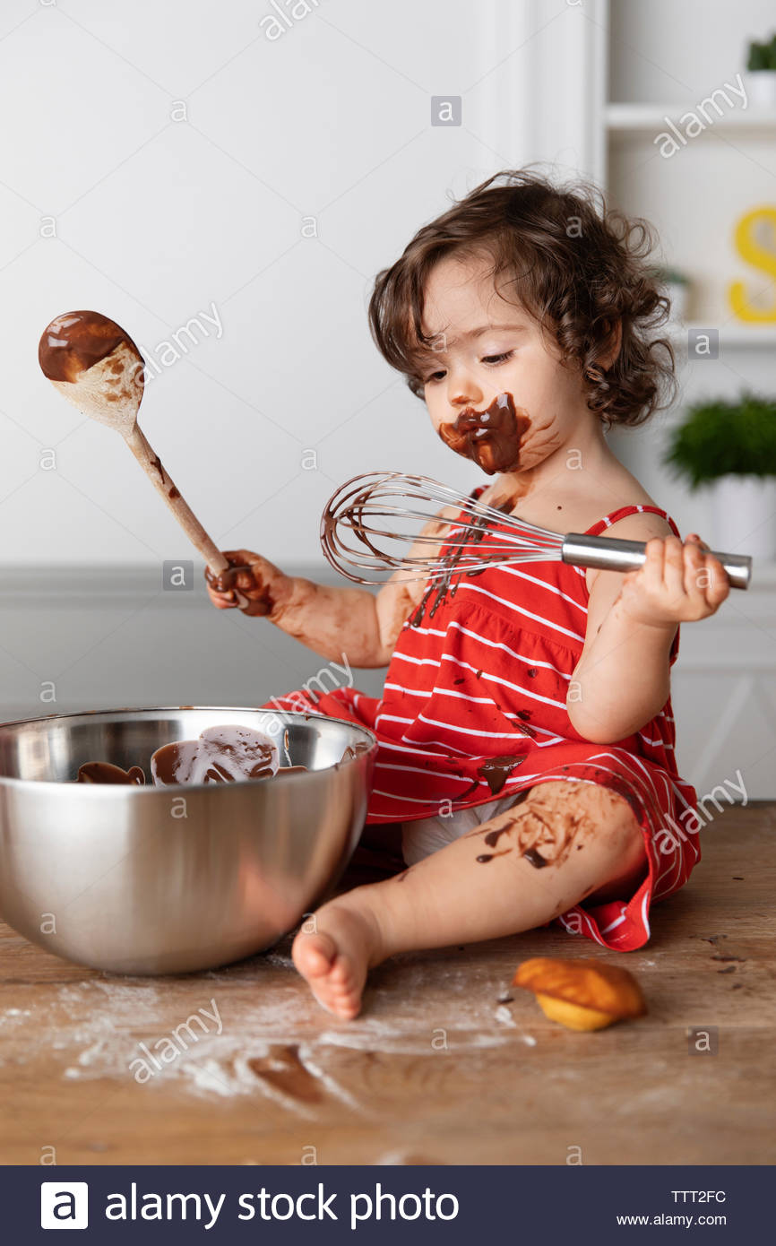 Cute baby girl eating chocolate while sitting with kitchen utensils on wooden table against wall at home - Stock Image