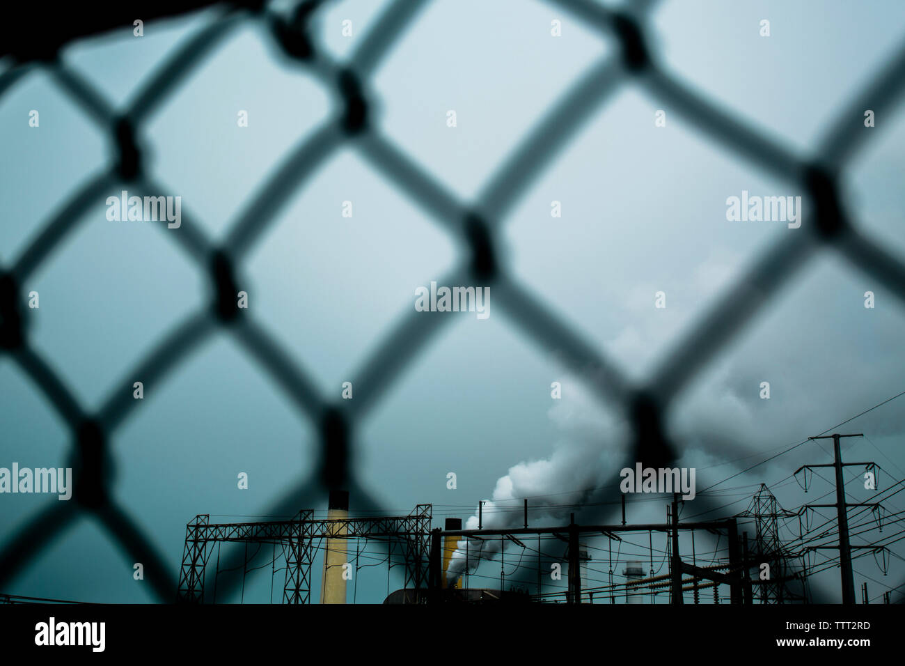Smoke emitting from factory seen through chainlink fence against sky Stock Photo
