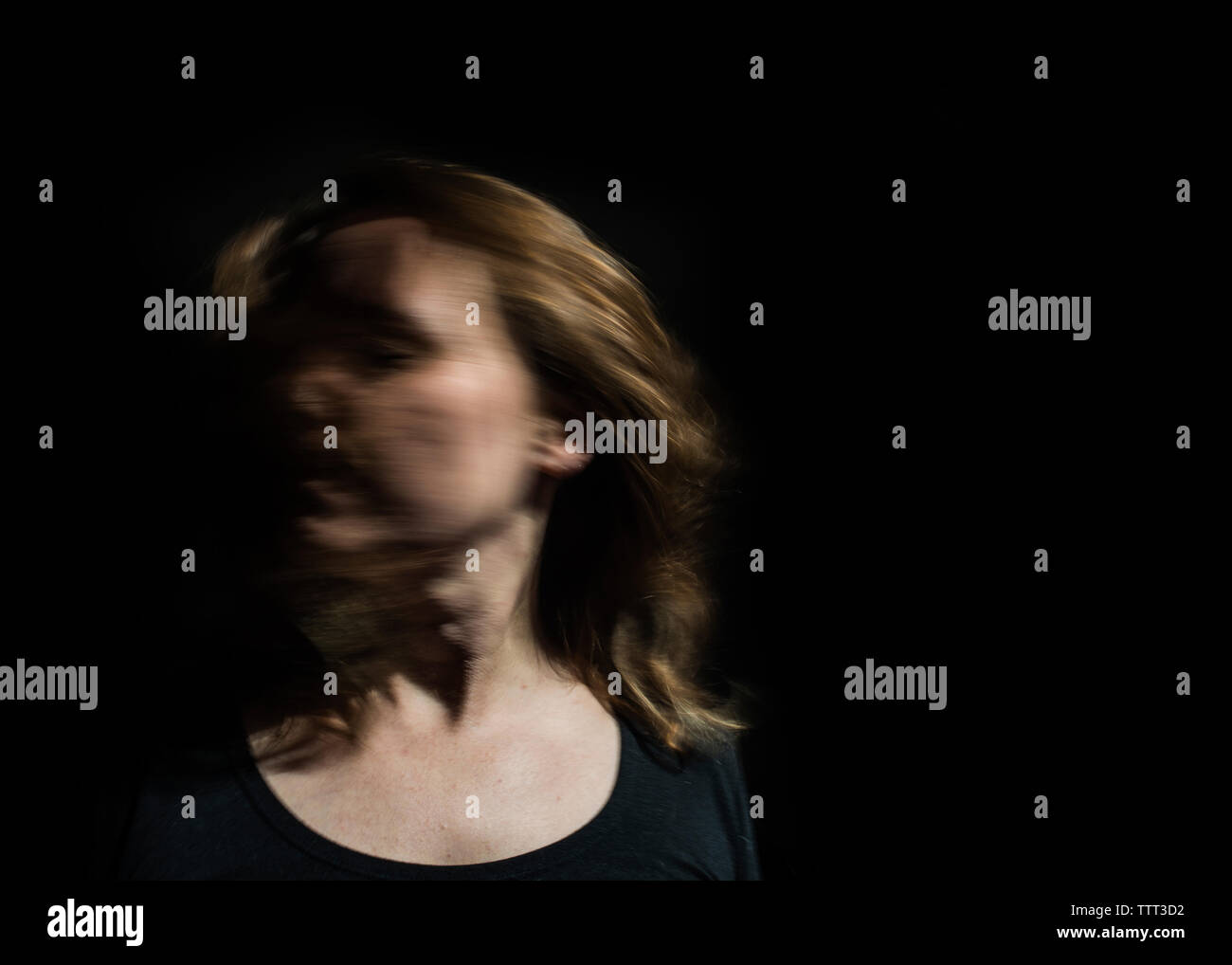 Close-up of woman shaking head while standing against black background - Stock Image