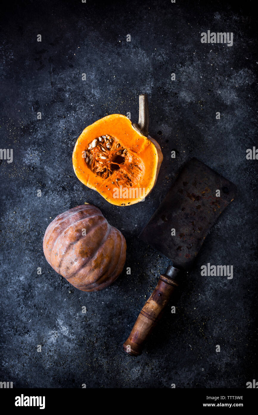 High angle view of pumpkin with cleaver on slate - Stock Image