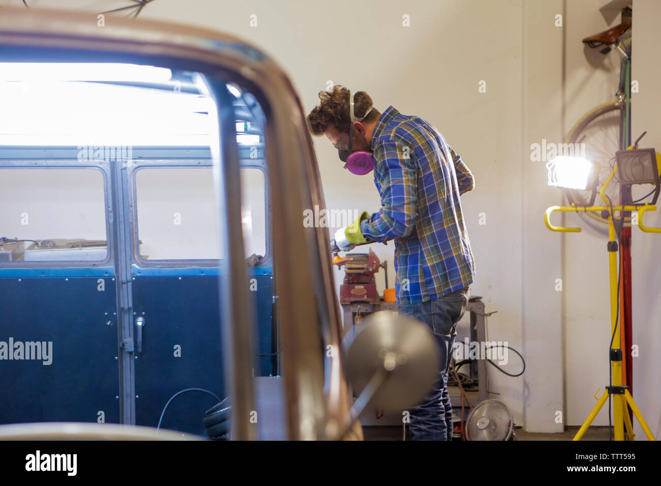 Side view of engineer polishing van with angle grinder in factory - Stock Image