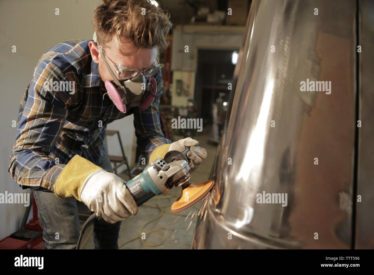 Engineer polishing damaged van with angle grinder in factory - Stock Image