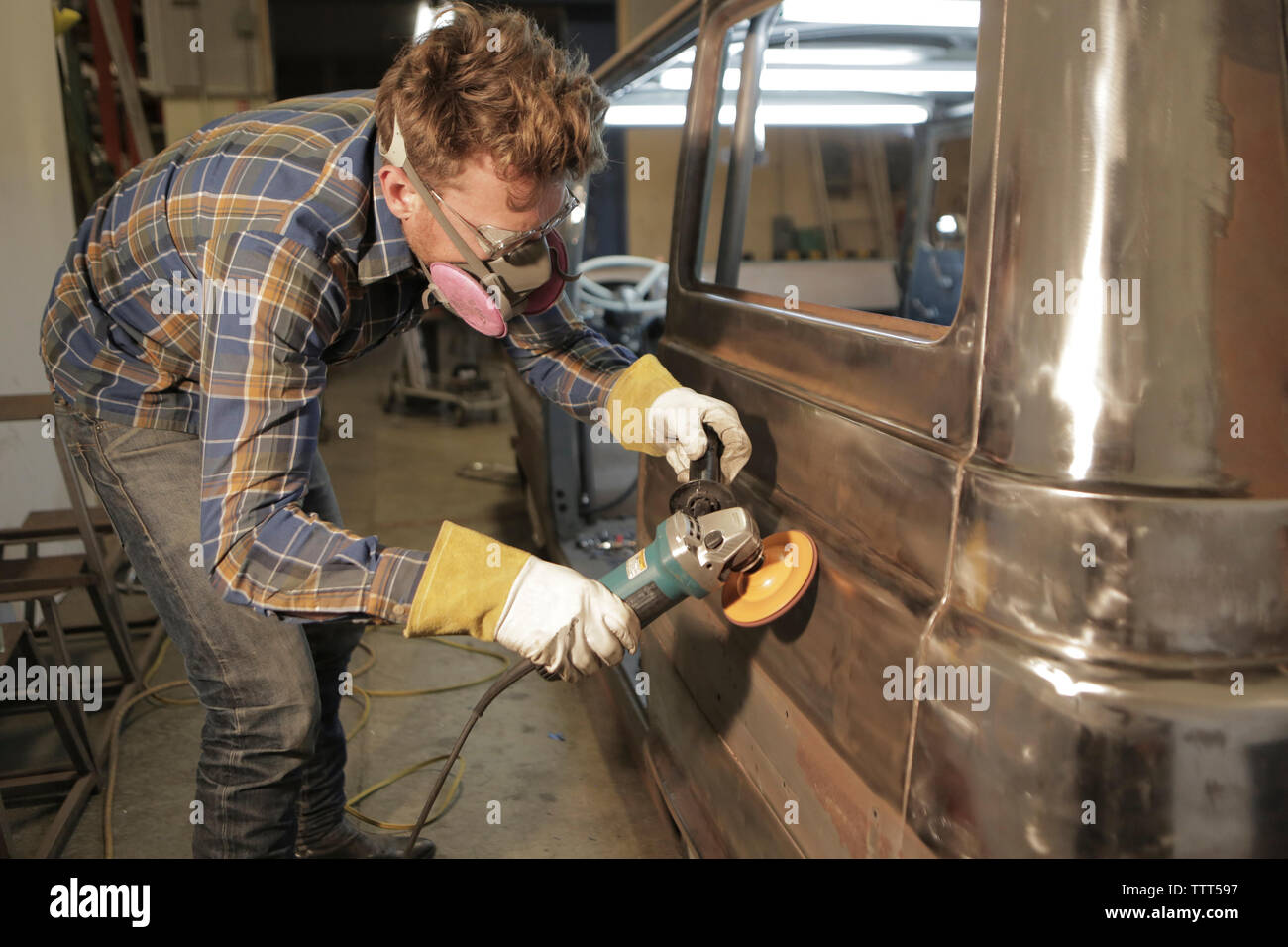 Engineer polishing van with angle grinder in factory - Stock Image