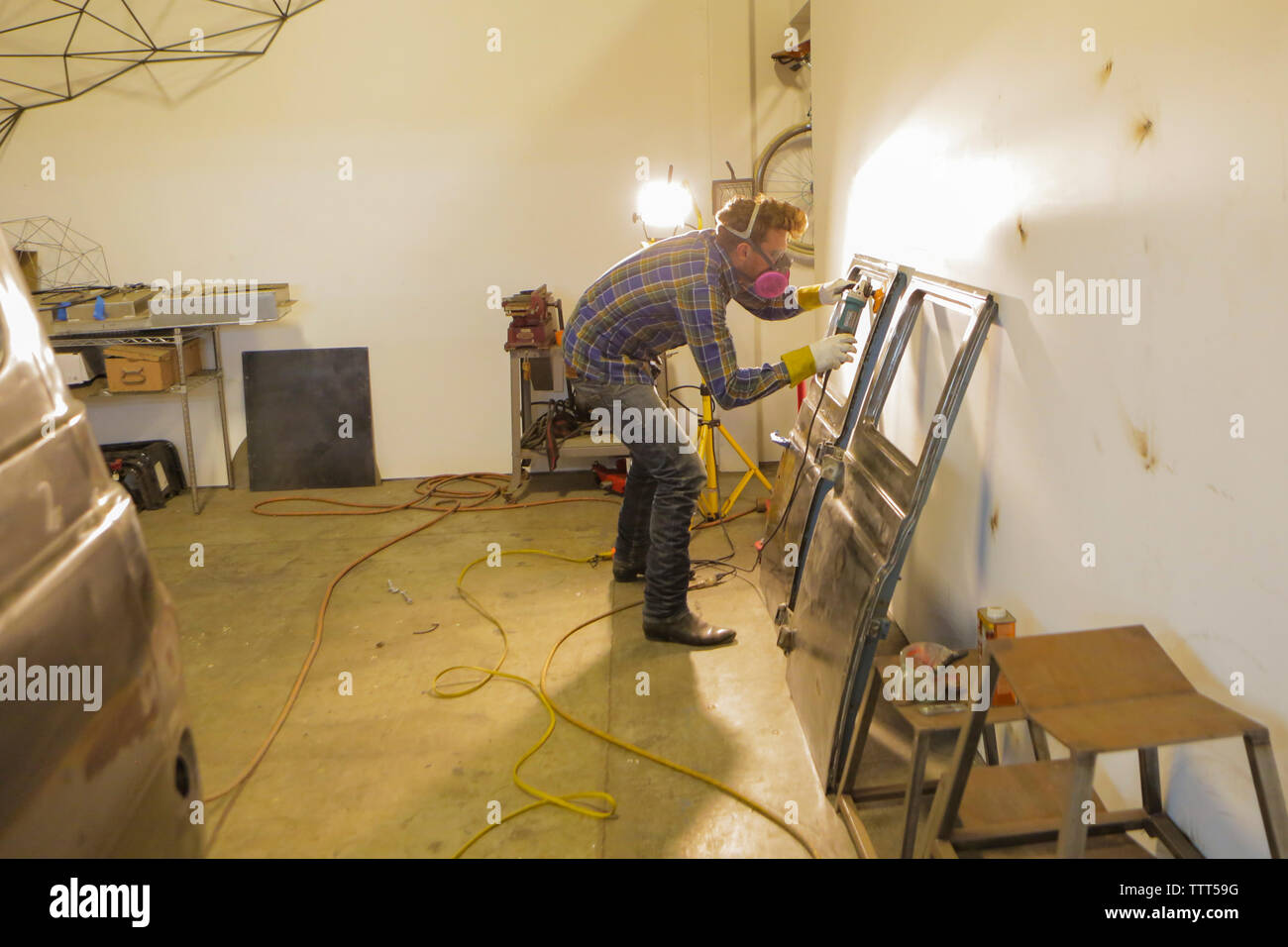 Engineer polishing van doors with angle grinder in factory - Stock Image