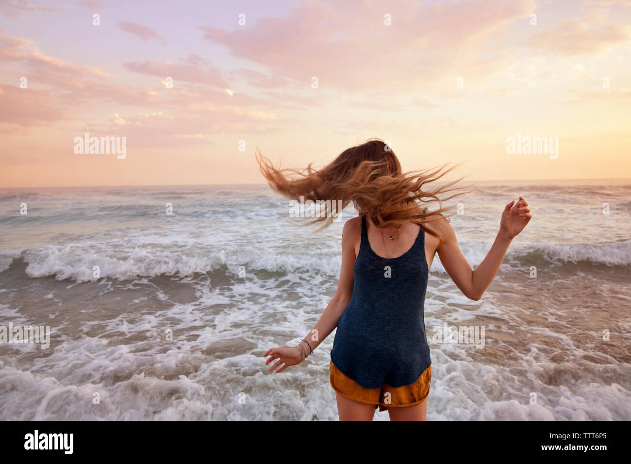 Woman tossing hair while standing at beach - Stock Image