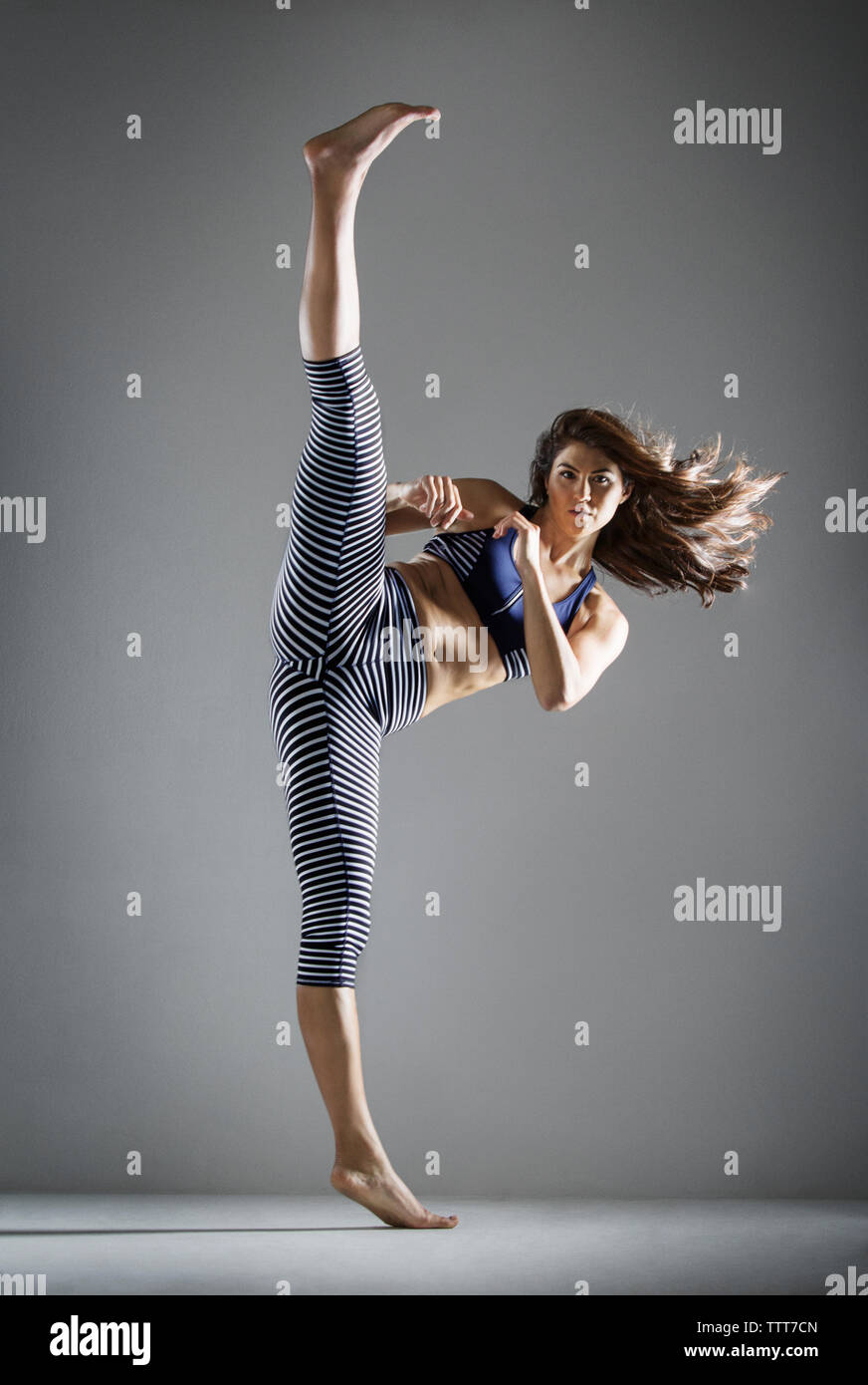 Portrait of woman practicing kick against gray background - Stock Image