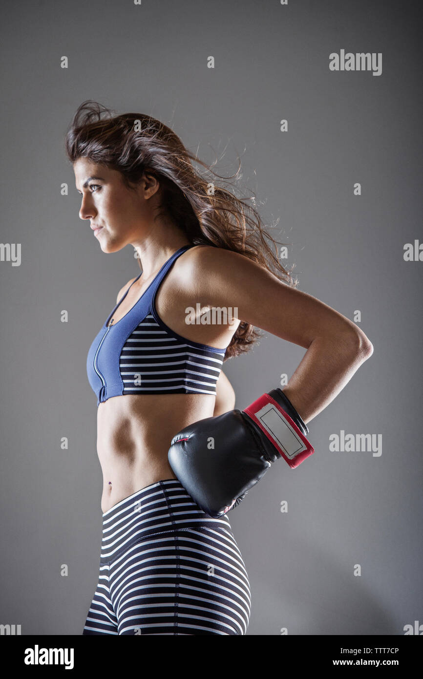 Woman with boxing gloves looking away while standing against gray background - Stock Image