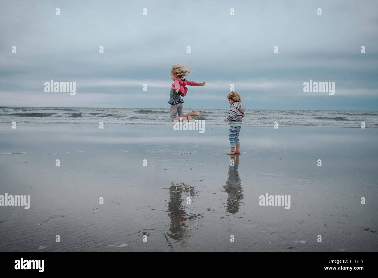 Carefree girl jumping while sister standing at beach against sky - Stock Image