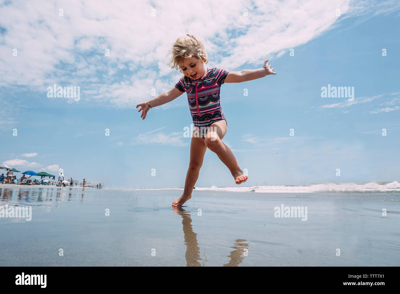 Low angle view of carefree girl playing at beach against cloudy sky - Stock Image