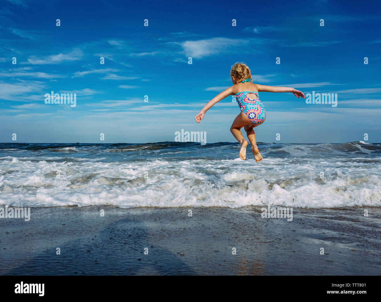 Full length of playful girl with arms outstretched jumping over shore against sky - Stock Image
