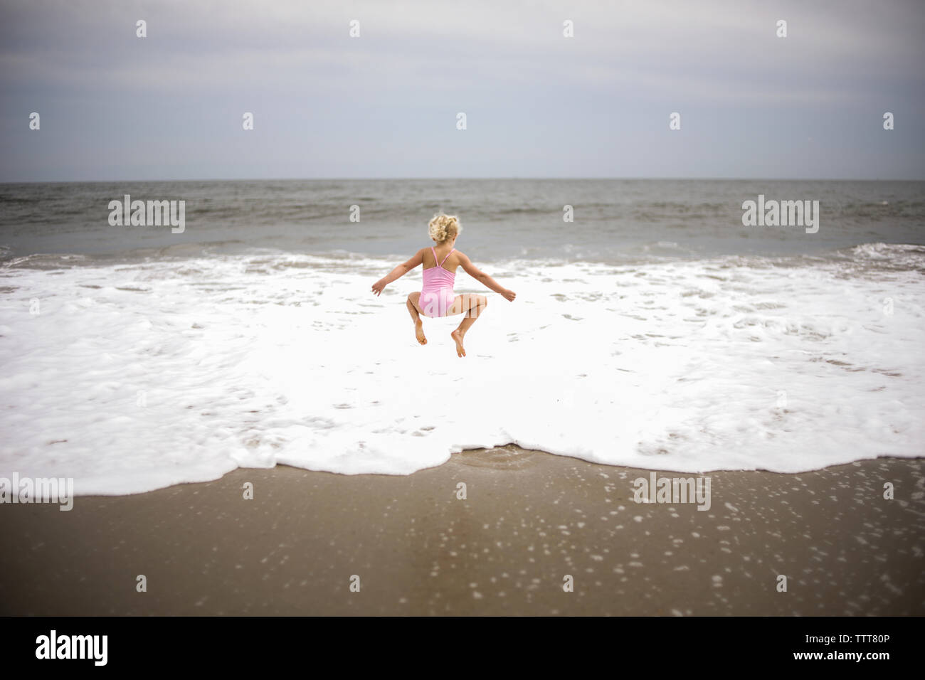 Rear view of playful girl jumping on shore at beach against sky - Stock Image