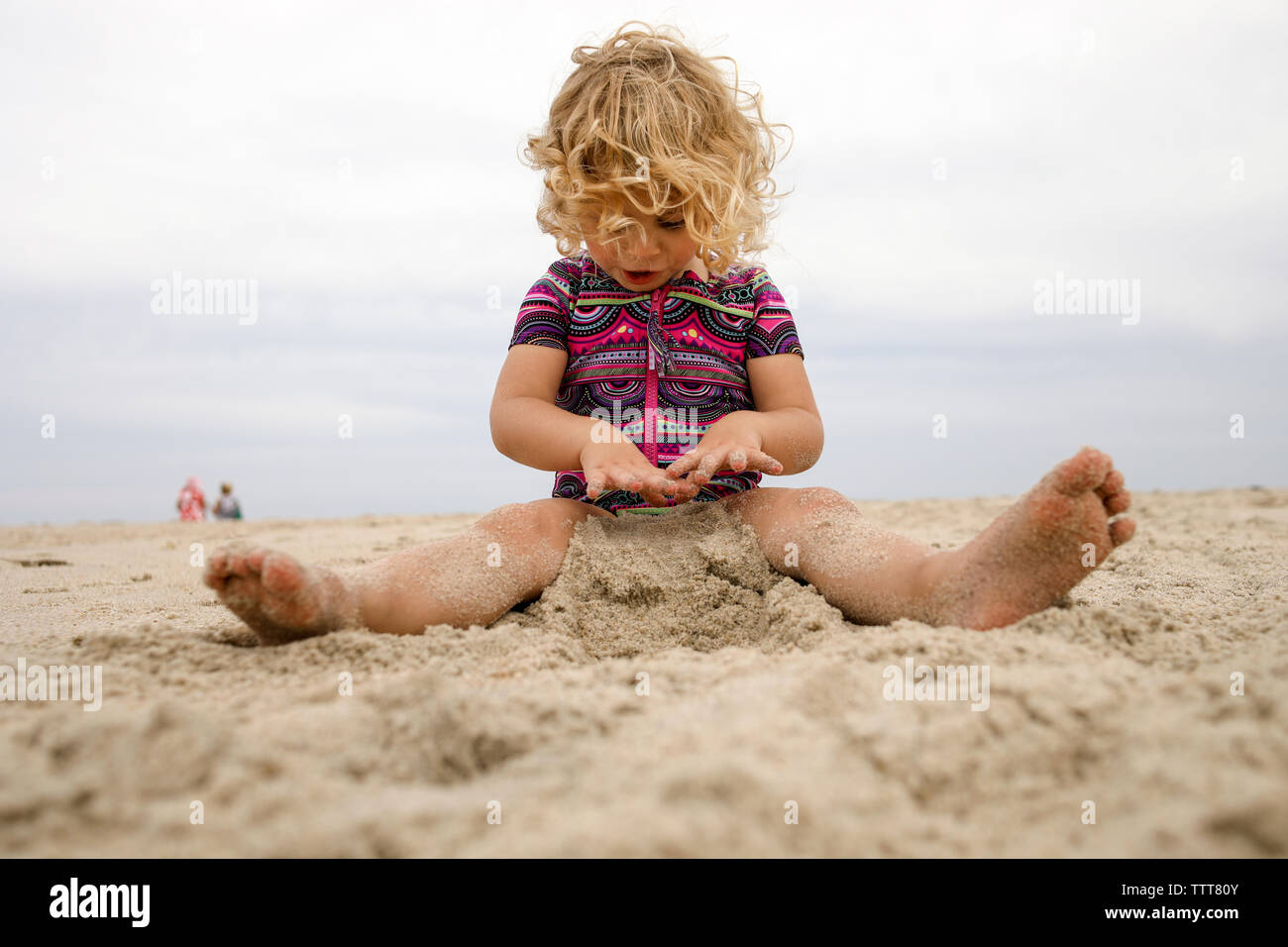 Full length of girl playing with sand at beach against sky - Stock Image