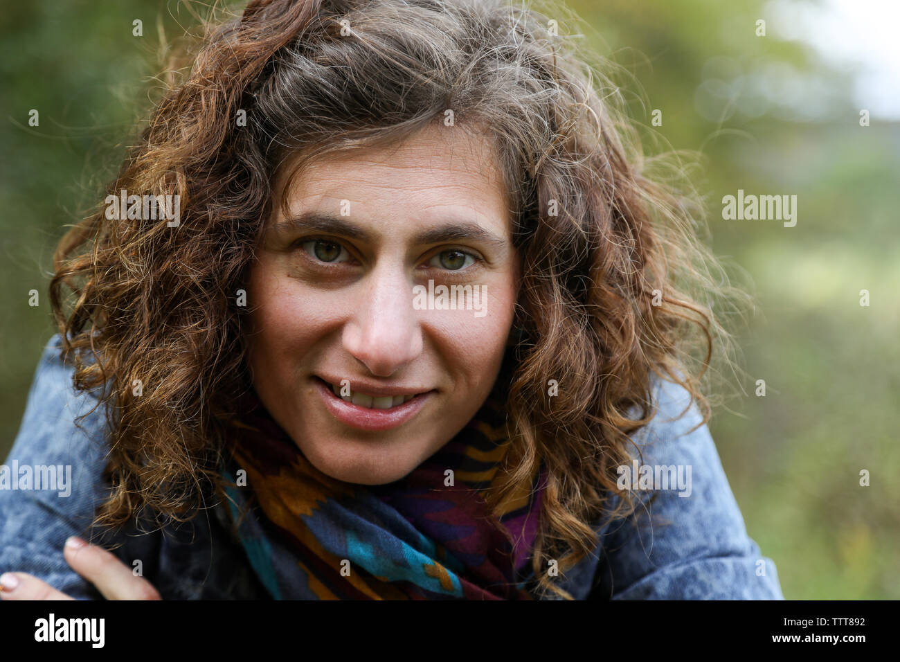 close up of woman with curly brown hair wearing scarf Stock Photo