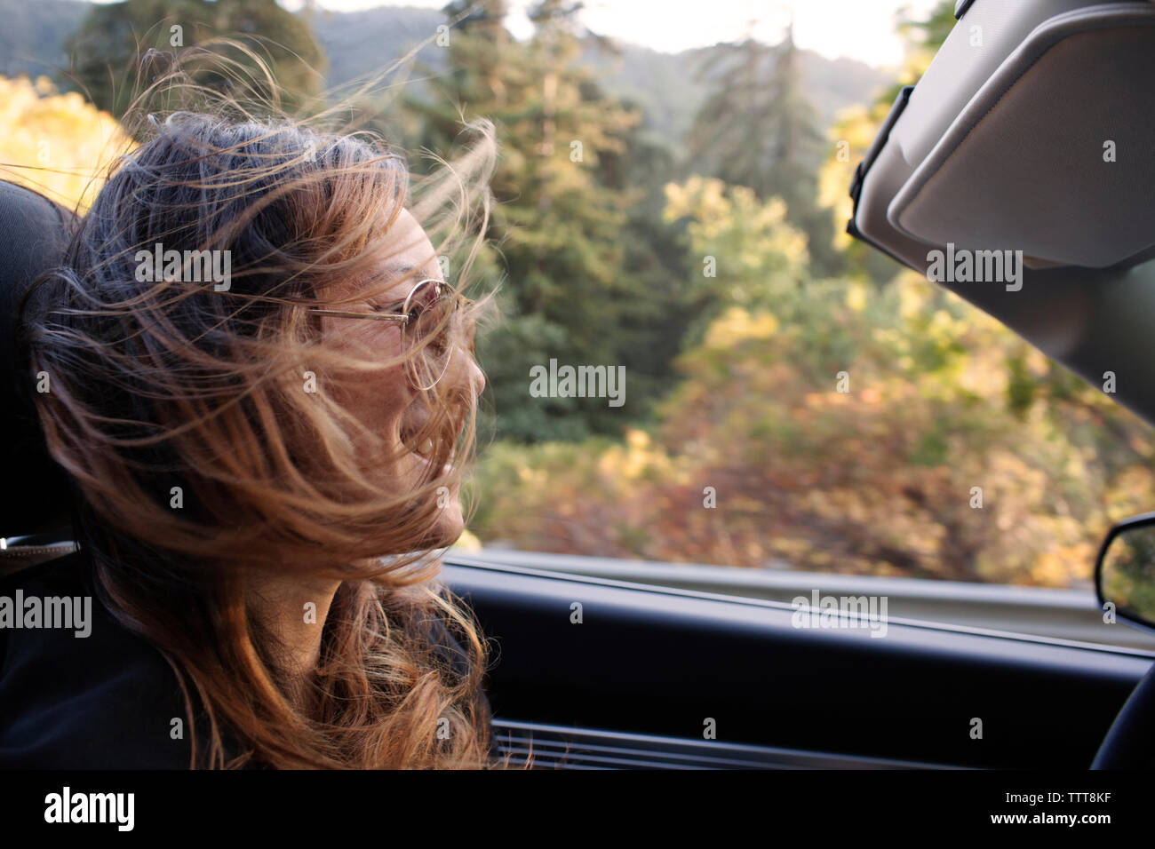 Happy woman with tousled hair riding in convertible car - Stock Image