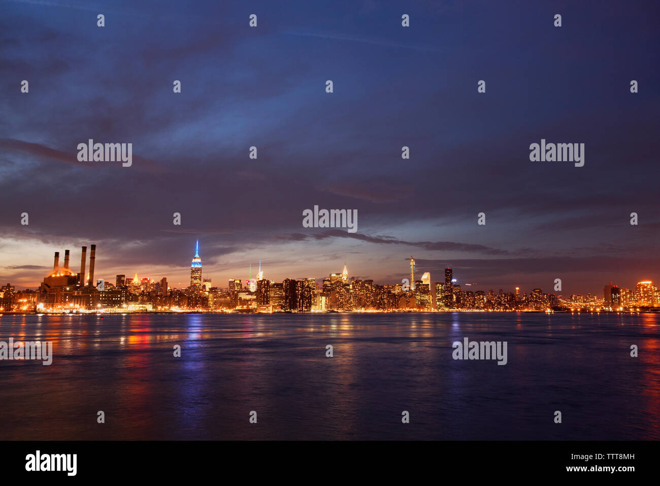Scenic view of river and illuminated cityscape against cloudy sky at night - Stock Image