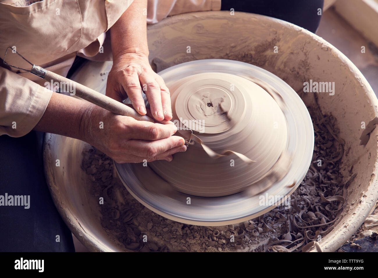 High angle view of woman molding shape to clay with work tool on pottery wheel - Stock Image