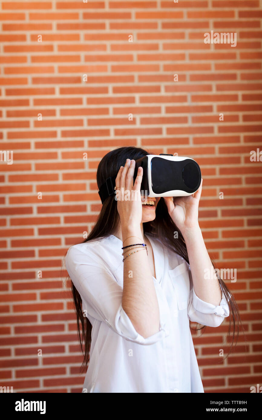 Smiling young woman using virtual reality simulator against wall at home - Stock Image