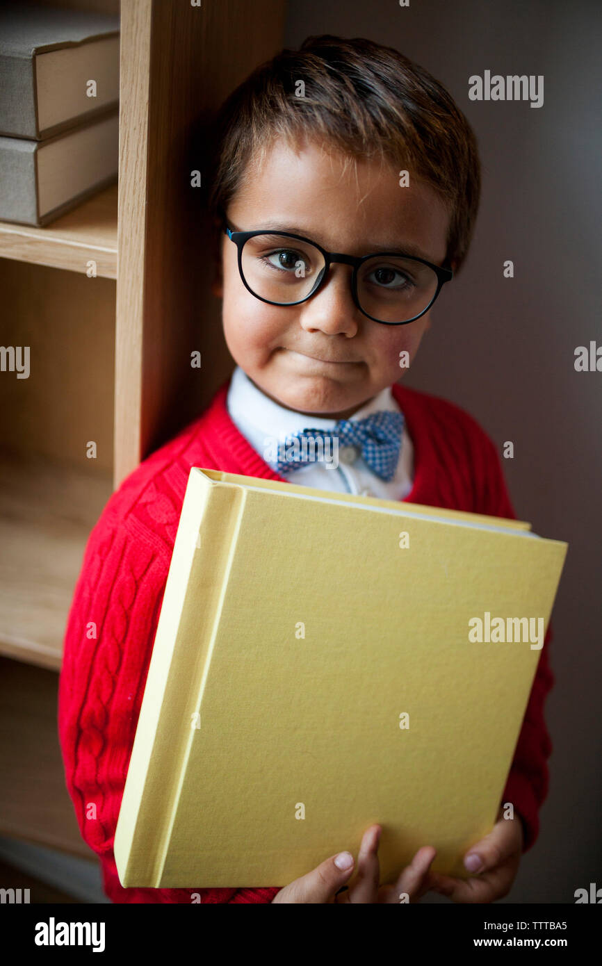Portrait of cute boy wearing eyeglasses and bow tie while holding book at home - Stock Image