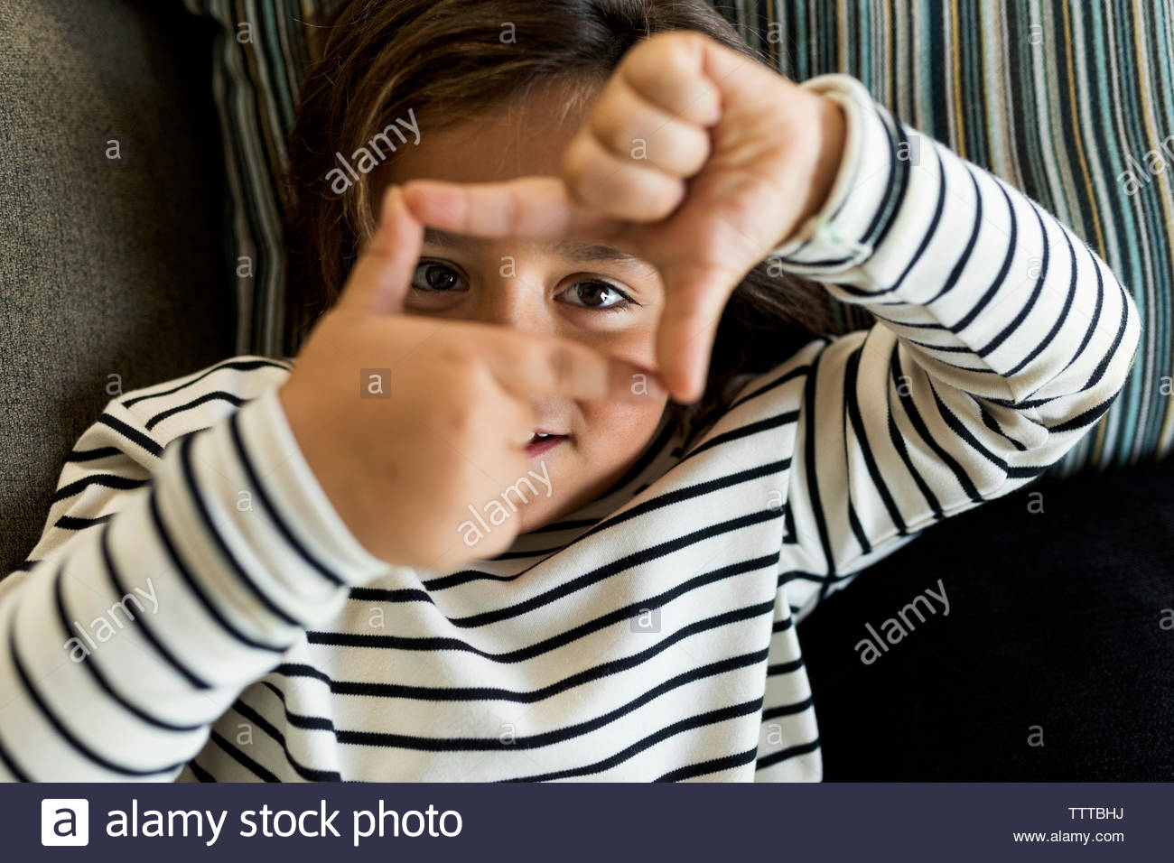 Cute little boy with striped top making a rectangle with his hands Stock Photo