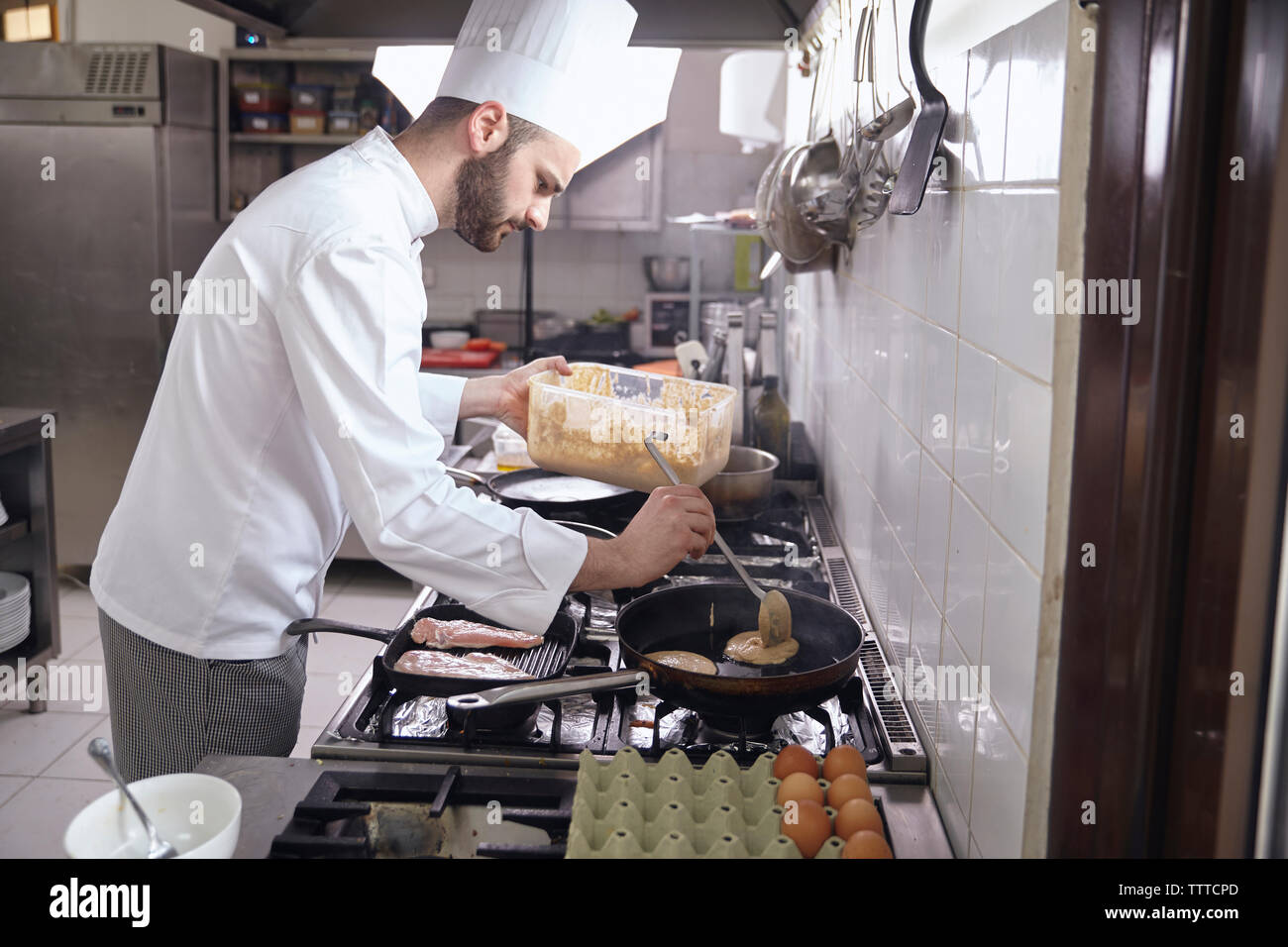 Side view of chef cooking pancake in frying pan on stove at commercial kitchen - Stock Image