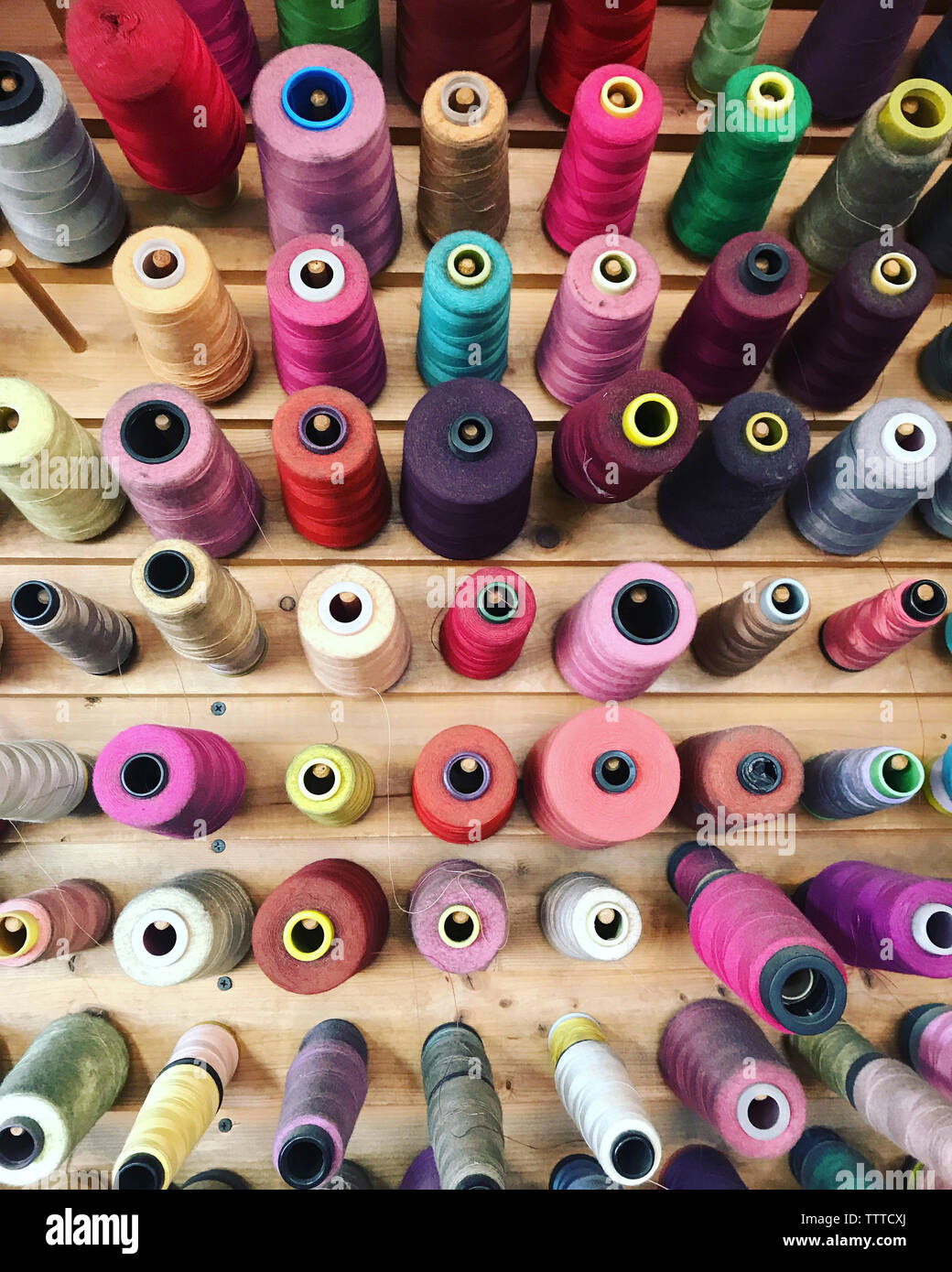 High angle view of colorful spools in wooden table - Stock Image