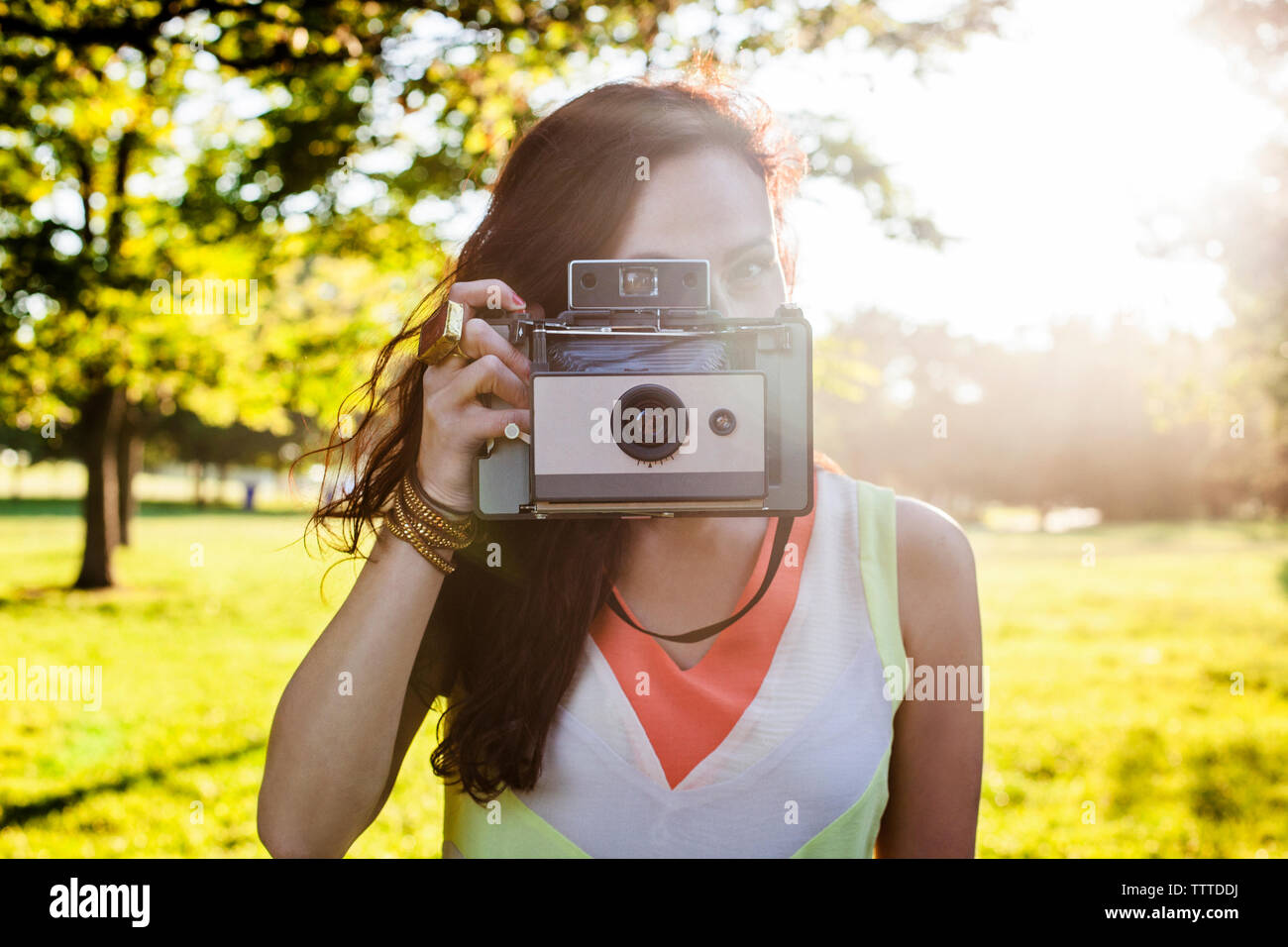 Young woman photographing with vintage camera - Stock Image