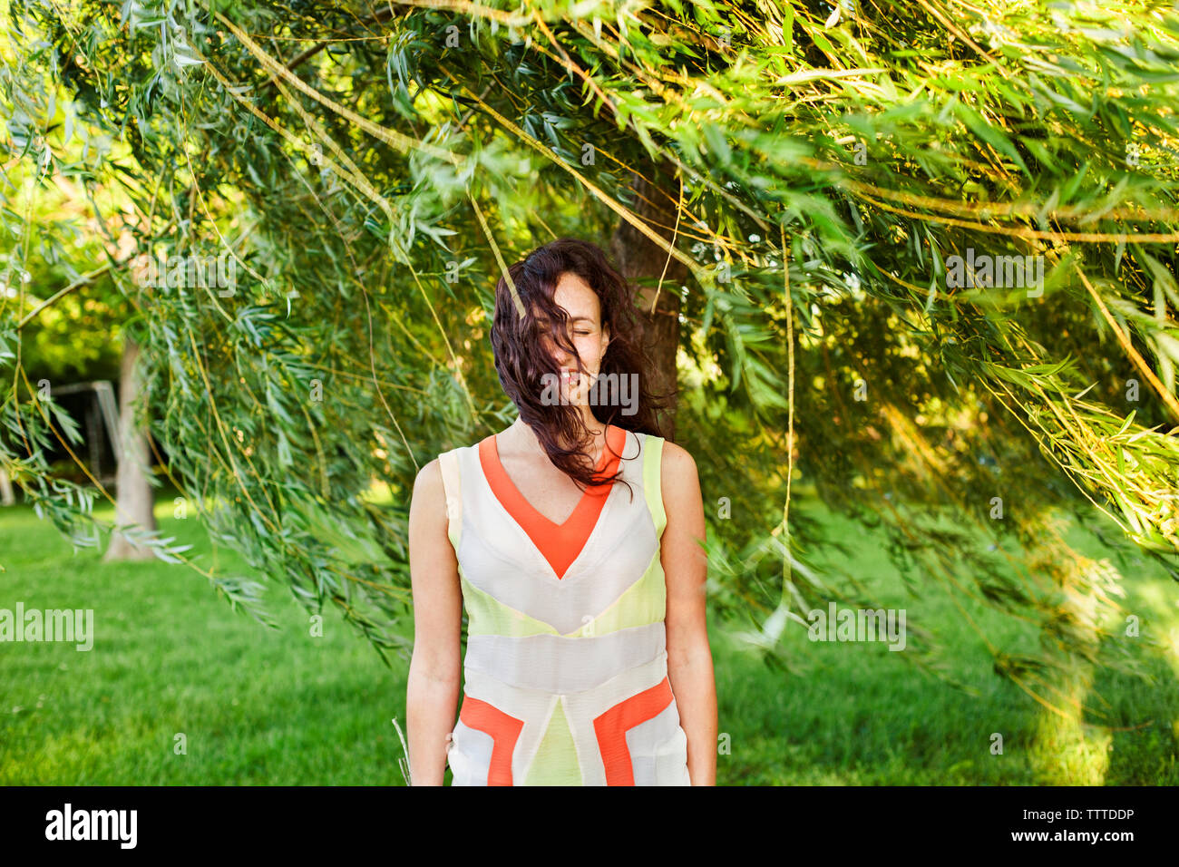 Happy woman standing under branches on field - Stock Image