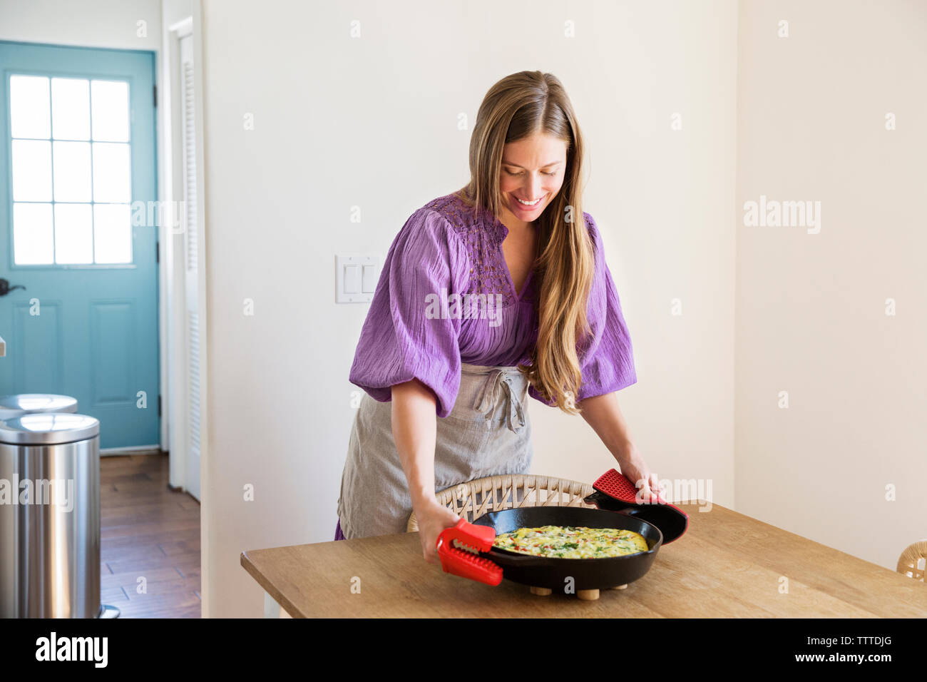 Happy woman holding hot cooking pan with omelet on table - Stock Image