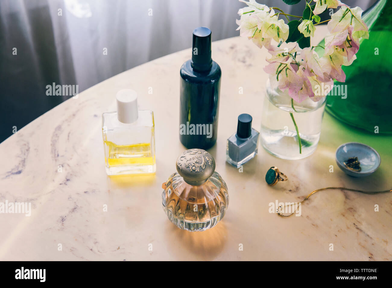 High angle view of beauty products with jewelry by flower vase on table Stock Photo