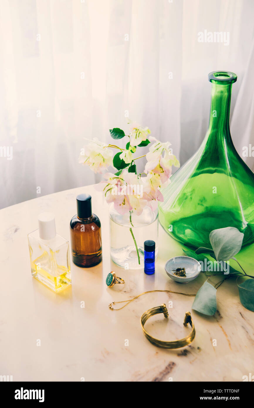 High angle view of beauty products and jewelry by flower vase on table Stock Photo