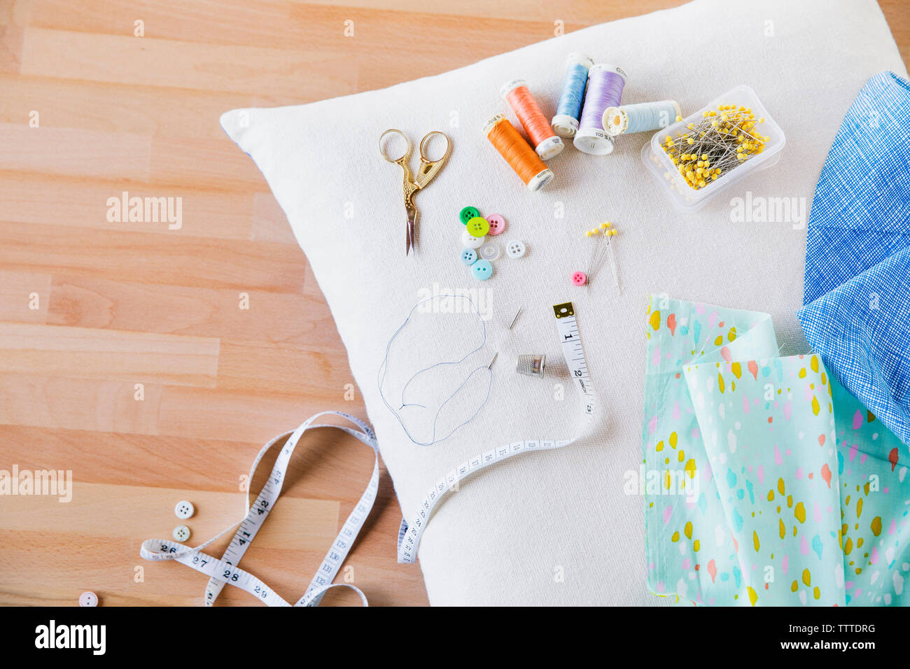 Overhead view of sewing item on pillow at table - Stock Image