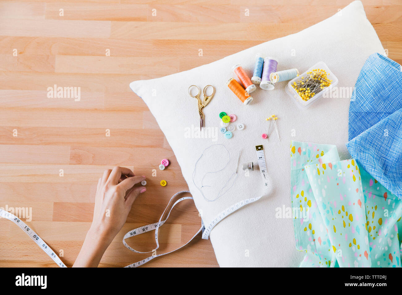 Overhead view of woman touching button by sewing item on pillow at table - Stock Image