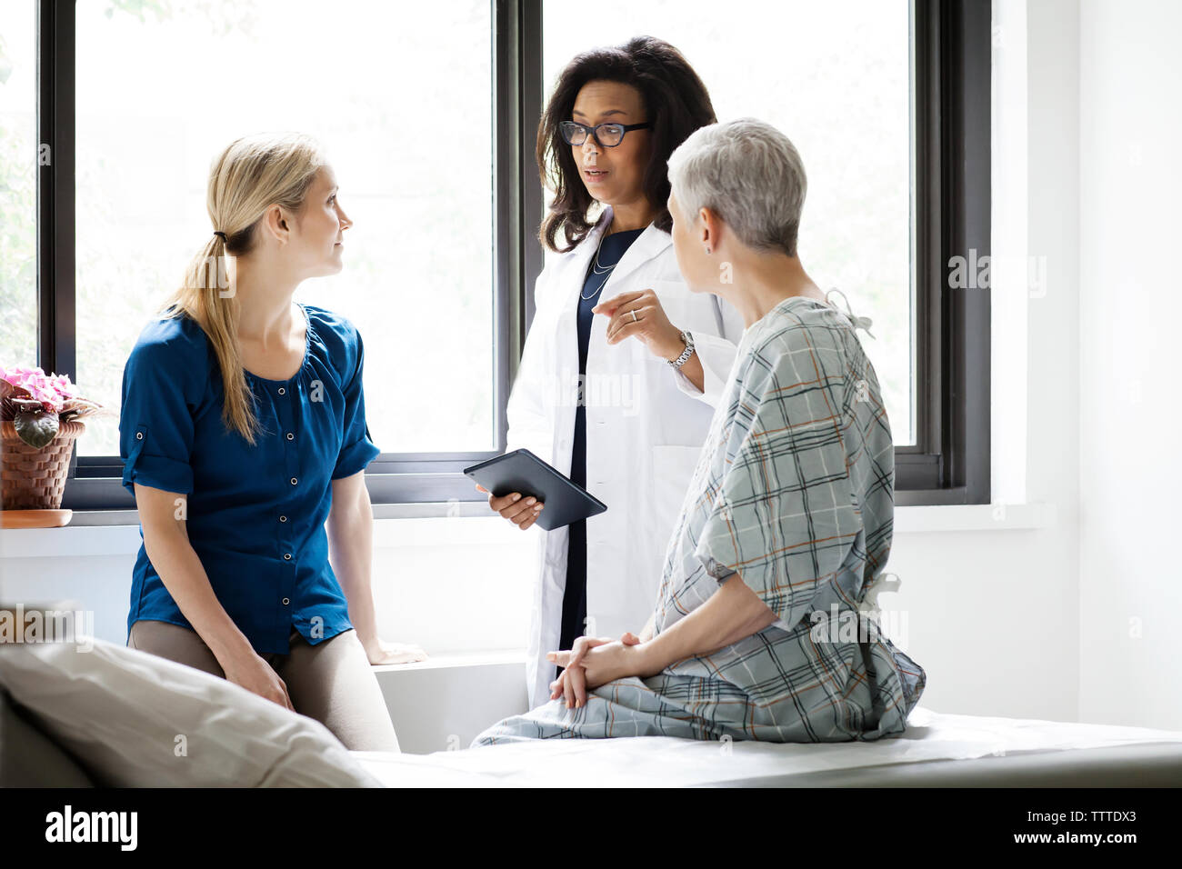 Doctor having discussing with woman and mature female patient in hospital Stock Photo