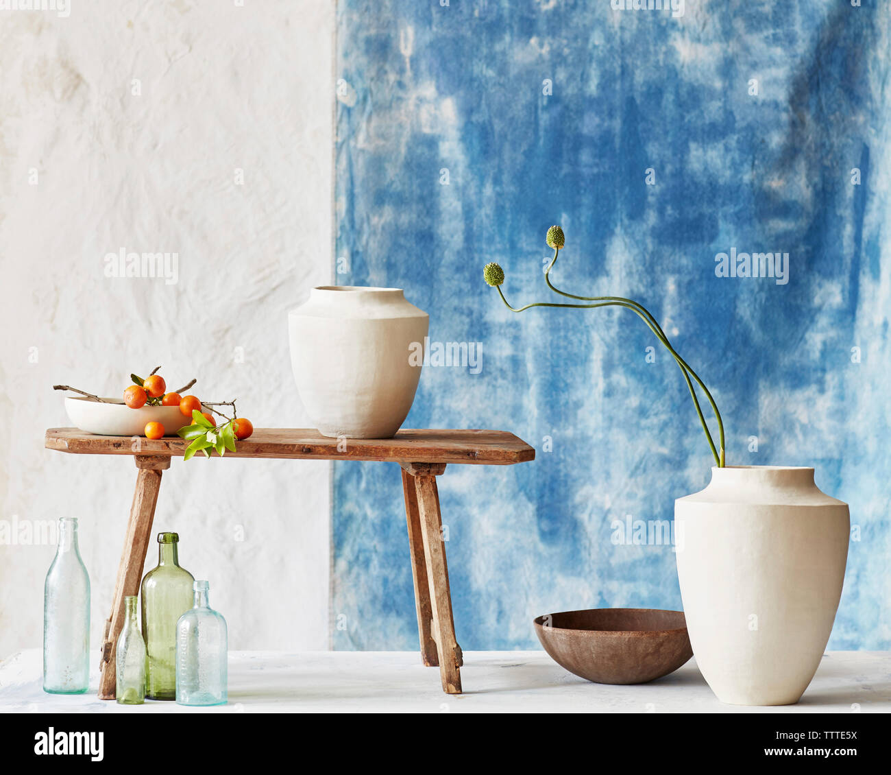 Vases with empty bottles and cherry tomatoes on table against wall Stock Photo