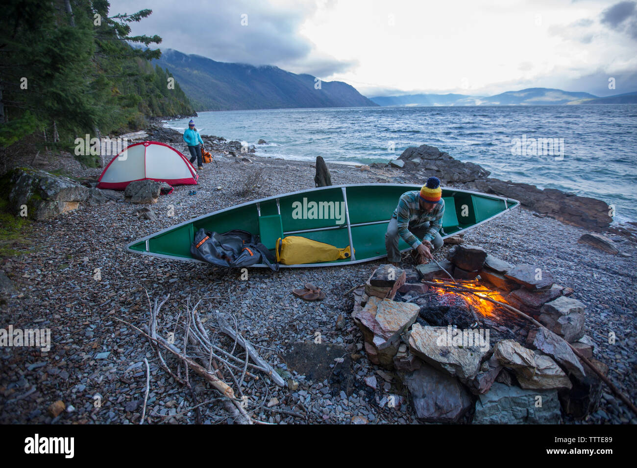 Couple canoe camping with campfire on Lake Pend Oreille, Idaho. Stock Photo