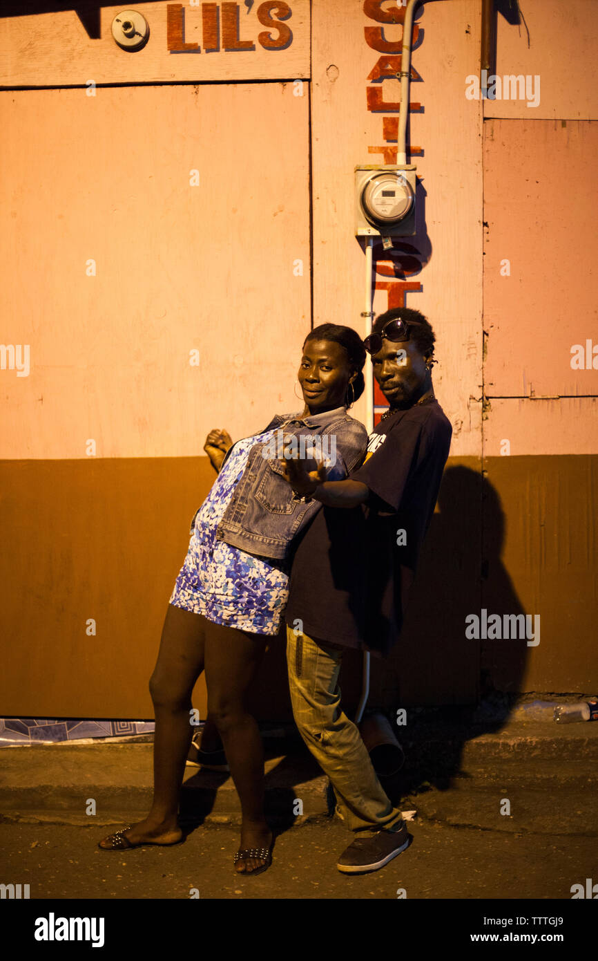 JAMAICA, Port Antonio. A local couple dancing and posing for a portrait in the city center at night. - Stock Image