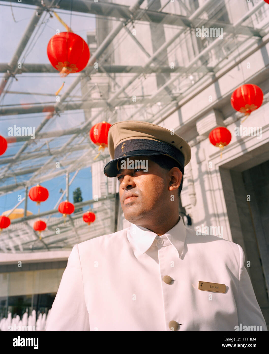 SINGAPORE, Asia, bellboy looking away outside Fullerton Hotel - Stock Image