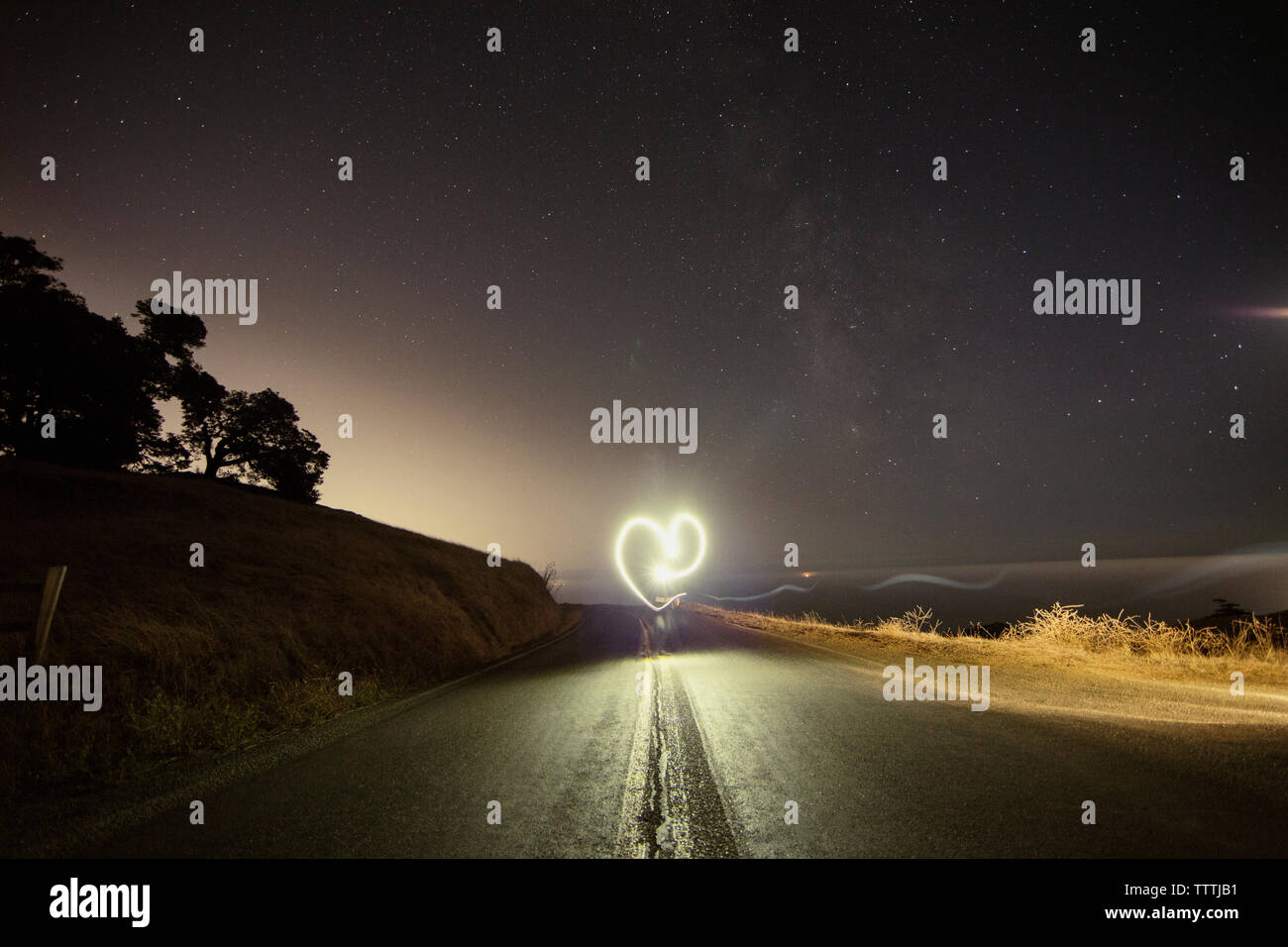 Person making heart shape while performing light painting on mountain road at night - Stock Image