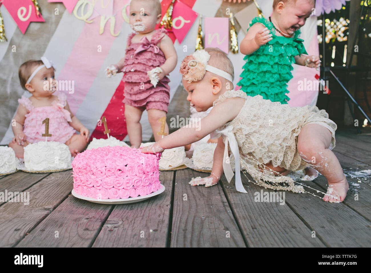 Baby girls with birthday cakes on floorboard at party - Stock Image