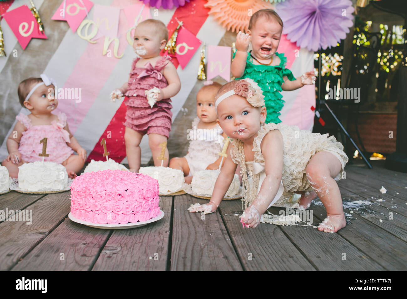 Baby girls with birthday cakes on floorboard - Stock Image