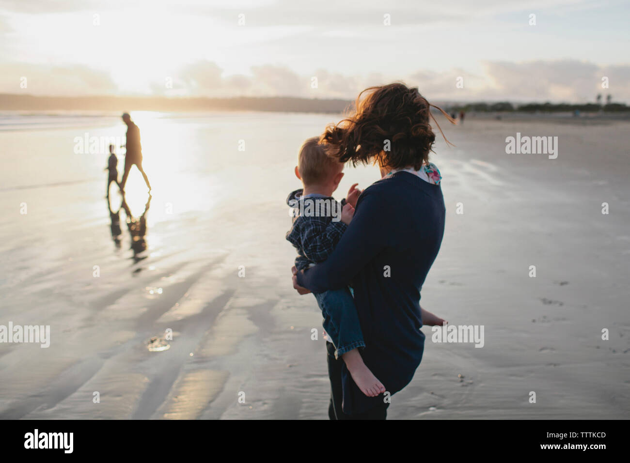 Side view of mother carrying boy looking at family walking at beach - Stock Image