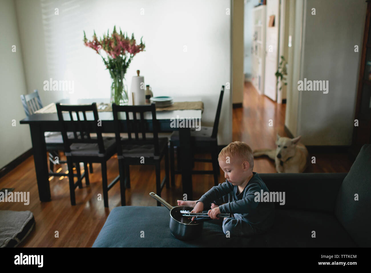 Baby boy playing with kitchen utensils while sitting on sofa at home - Stock Image