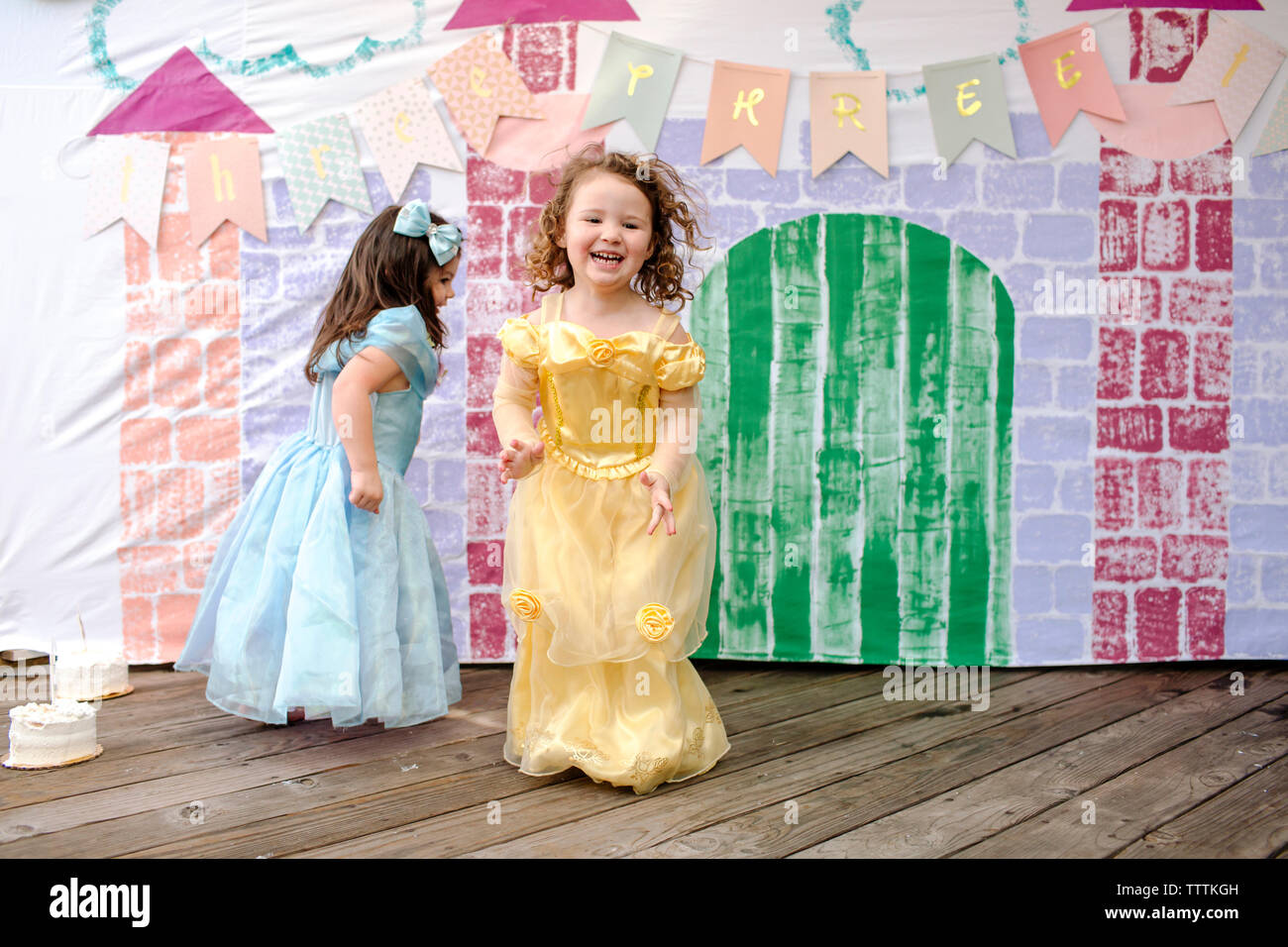 Full length of girls playing on floorboard against castle painting during princess party - Stock Image