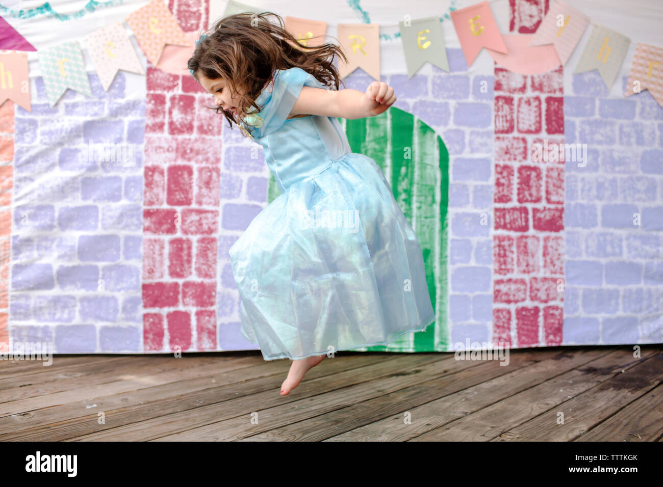 Side view of girl jumping on floorboard against castle painting during princess party - Stock Image