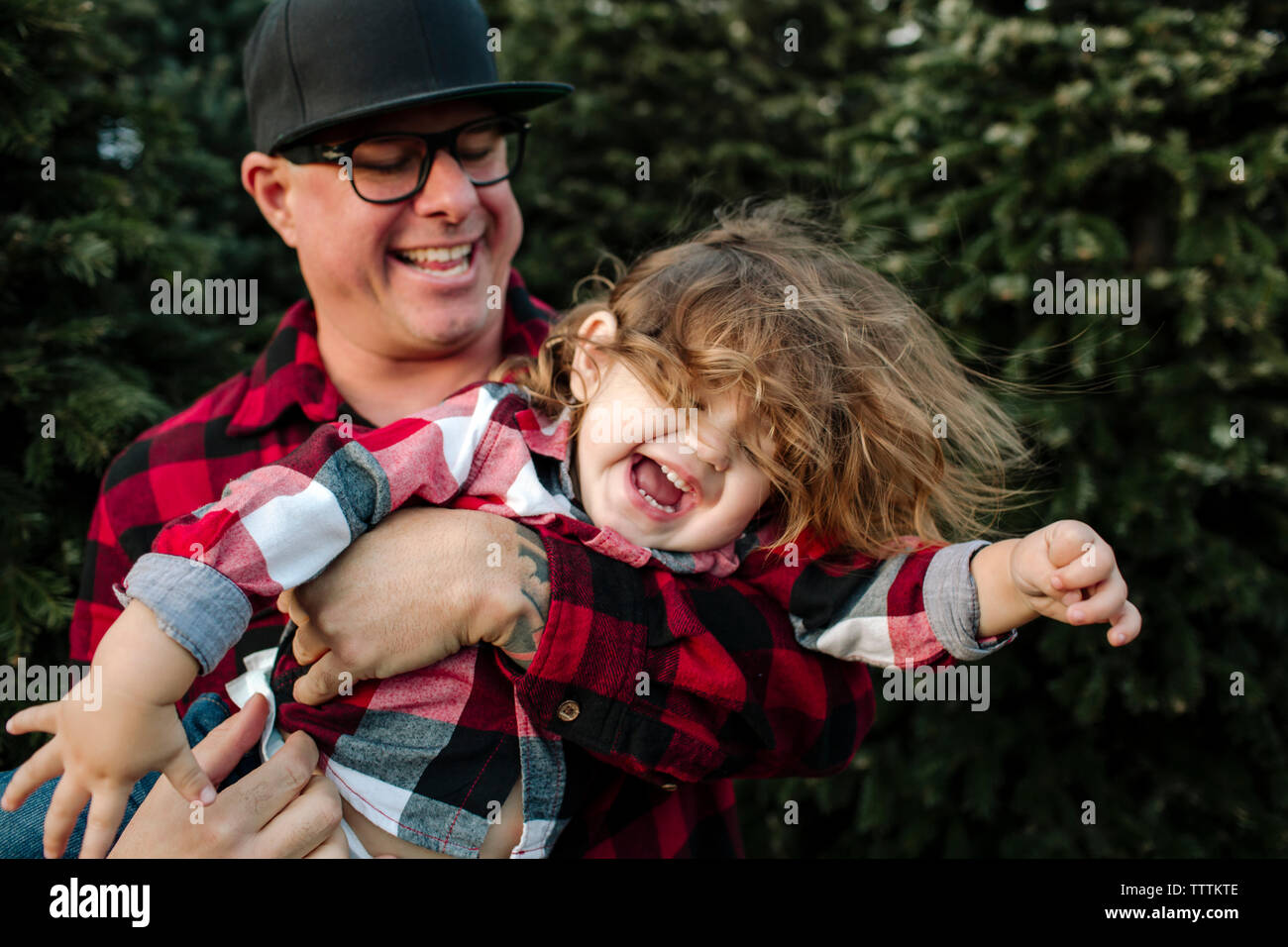 Playful father carrying cheerful son against Christmas Trees - Stock Image