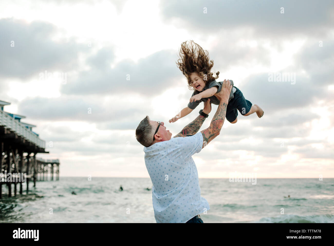 Playful father throwing son in air while playing against cloudy sky at beach - Stock Image
