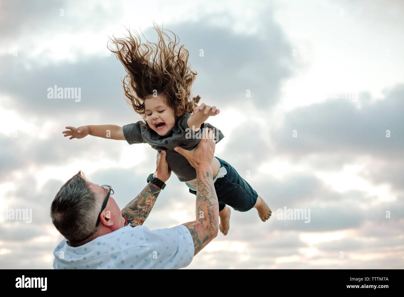 Low angle view of playful father throwing son in air while playing against cloudy sky at beach - Stock Image