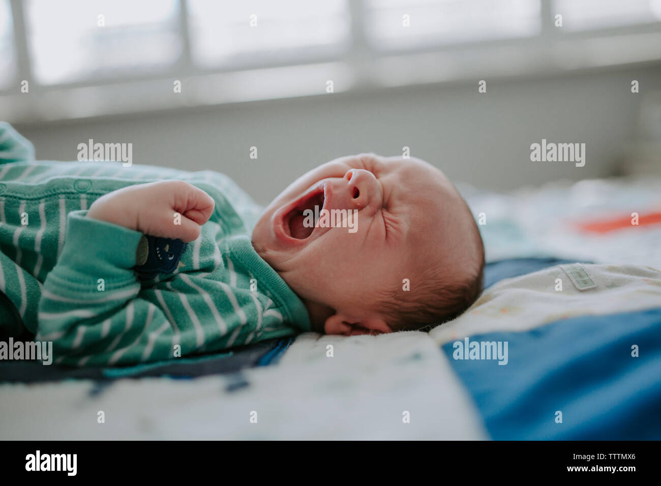 Close-up of baby boy yawning while sleeping on bed at home - Stock Image